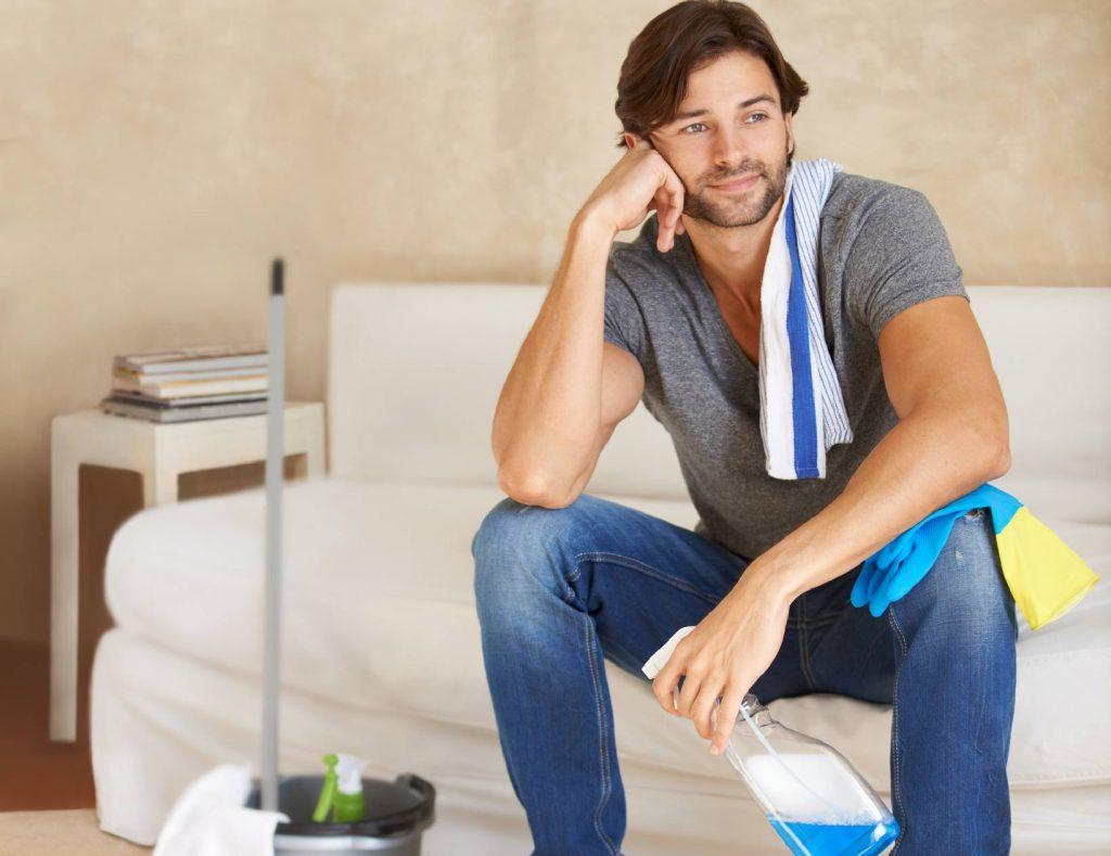 homem limpando sofá da casa